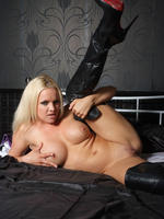 Frankie gets naked on her big bed but keeps her leather boots on