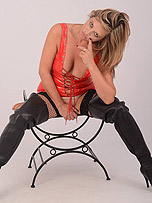 Hot blonde Milf Louise teases in tight red latex and black thigh high boots with slutty fishnet stockings underneath