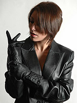 Gorgeous brunette in sexy black leather jacket accompanied by a pair of soft leather gloves