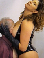 Mistress Gill decides to treat her slave to a little glove over mouth and nipple torture. Then she shoves his face into her big boobs while stroking his head with her black soft leather gloves, before trampling his balls